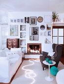 Sitzbereich mit Sofa und Ohrensessel am Kamin in weihnachtlich dekoriertem weißen Wohnzimmer