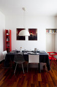 Dining table set with black tablecloth in interior with white walls and red accents of colour