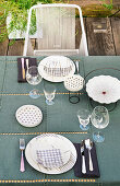 Table set in blue and white on terrace and designer chair with strung cord backrest and seat