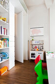 Toy kitchen, shelves and colourful children's chairs in children's bedroom