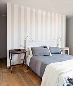 Double bed against grey-and-white striped partition