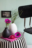Anemone in vase on black-and-white striped side table