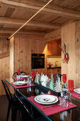 Festively set table and black chairs in dining area of chalet