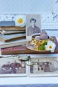 Goldene Kaffeetasse mit Pralinen und Rosenblüten, alte Bücher und Taschenuhr