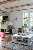 Autumn arrangement on white coffee table in bright, open-plan, shabby-chic living room
