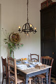 Rustic dining table and various chairs below wrought-iron chandelier