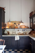 L-shaped kitchen counter and chequered floor below pendant lamps in kitchen of period building