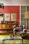 Patterned armchair in front of botanical illustrations on coral-red wall
