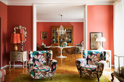 Patterned armchairs in living room in front of open doorway leading in dining room