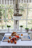 Dining table with decorative linen place mats and crystal chandelier in front of window