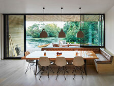 Dining table, shell chairs and corner bench next to glass wall