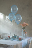 Three balloons floating above table set in pale blue and pink