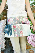 Woman wearing pretty, floral gardening apron holding hydrangeas