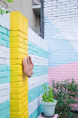 Brightly painted brick wall of urban courtyard garden