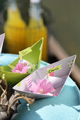 Paper boats and garden flowers as place names for picnic on lake
