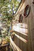 Holzverfassade eines Tiny Houses mit runden Bullaugenfenstern