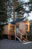 Tiny House aus Holz auf Stelzen mit Treppenaufgang und kleiner Veranda
