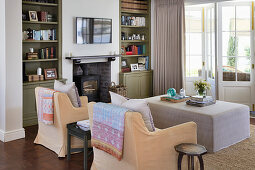 Fireplace flanked by green fitted bookcases in living room