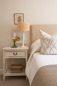 Bed and bedside table in guest bedroom in muted beige and white