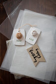 Gift tags with flower motifs and birthday greeting lying on tissue paper