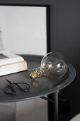 Scissors, light bulb and book on round, charcoal-grey side table