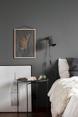 Dried plant in picture frame on grey wall above bedside table in bedroom