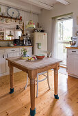 Wooden table with floor-protection socks in cosy country-house kitchen