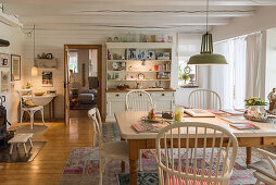 Spoke-back chairs around table and dresser in country-house-style dining room