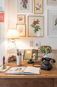Vintage-style floral pictures above old telephone on wooden table
