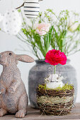 Blown egg and ranunculus in Easter nest next to bunny figurine