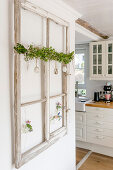 Old window decorated with garland of box, Easter eggs and suspended vases hung on wall and view into kitchen