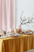Easter table set in feminine style in shades of ochre and pink