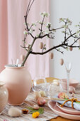 Wooden eggs hung from flowering branch in vase on Easter table set in pink