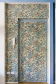 Door and niche covered in floral wallpaper in shades of blue and orange