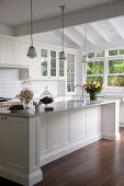 Glass vessels on white kitchen counter below pendant lamps