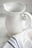 White jug and cloth on marble surface