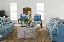 Blue sofas and chairs around coffee table in living room