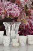 Tealight holders and vase in front of floral picture