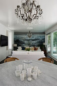 Dining table with marble top in front of lounge with maritime mural wallpaper