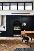 High, open living room with black fixtures and arched neckline