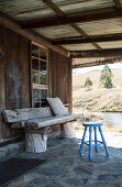 Wooden bench and stool on roofed terrace of rustic wooden cabin