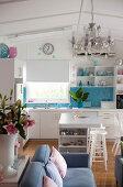 White open-plan kitchen with splashback of sky-blue mosaic tiles