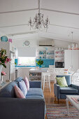 Blue-and-white interior with open-plan kitchen and seating area with couch and armchairs