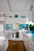 White cupboards and sky-blue mosaic-tiled splashback in kitchen