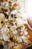 Christmas tree decorated with artificial snow and pink and champagne baubles