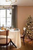 Christmas tree and festively set table in pink dining room