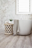 Ethnohocker neben freistehender Badewanne im minimalistischen Bad