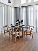 Designer chairs at round wooden table surrounded by glass walls with translucent curtains