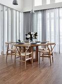 Designerstühle am runden Holztisch vor Fensterfronten mit Gardinen