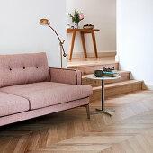 Dusky pink sofa on herringbone parquet floor next to steps leading to hallway